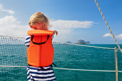 Little child in life jacket on board of sailing boat. Happy little baby in life jacket on board of sailing boat watching offshore sea and tropical islands on Royalty Free Stock Photos