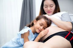 Little child listening baby in belly and hug mother with happiness in room. The little child listening baby in belly and hug mother with happiness in room stock images