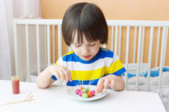 Little child with lollipops of playdough and toothpicks Stock Image
