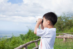 Little child look in binoculars outdoor in sunny summer day Royalty Free Stock Photography
