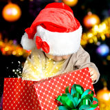Little child looking into the box with christmas gifts Stock Image