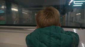 Little child looking out subway train window. Slow motion of a little boy traveling in city underground, back view through the window, oncoming train arriving to stock video