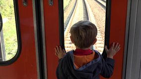 Little child looking out the train window, dreaming, get closer to destination. UHD 4K stock video footage