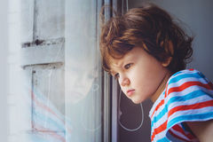 Little child looking out the window through the blinds. Backgrou Royalty Free Stock Photography