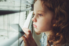 Little child looking out the window through the blinds. Background toning to instagram filter. Sad little girl looking out the window through the blinds stock photos