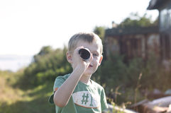 Little child looking at spyglass made from cardboard Royalty Free Stock Image