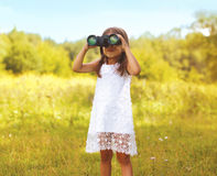 Little child looks in binoculars outdoors in sunny summer day. Outdoors Stock Images