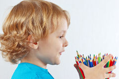 Little child looks on color pencils on white background Royalty Free Stock Photography