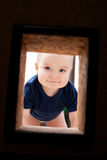 Little child looks to hole in the wall. Little funny child looks to hole in the wall stock images