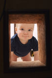 Little child looks to hole in the wall Stock Photo