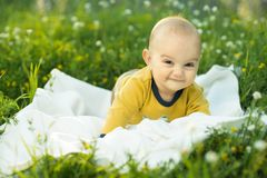 Little child lying on a diaper the grass Stock Images
