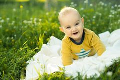 Little child lying on a diaper the grass. And smiling Royalty Free Stock Images