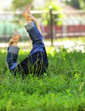 Little child lying on a green lawn Stock Images