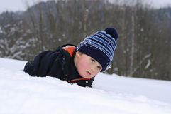 Little child lying on snow Royalty Free Stock Image