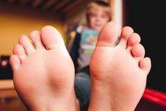 Little child lying on the wooden floor of his bedroom barefooted sensory connections. Little child lying on the wooden floor of his bedroom barefooted - sensory royalty free stock images