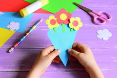 Little child made paper crafts for mother`s day or birthday. Child holds a paper bouquet in hands. Easy and beautiful gift for mom. Mother`s day paper gift Royalty Free Stock Photos