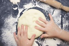 Little child making dough for backing. Kid`s hands, some flour, wheat dough and rolling-pin on the black table. Children hands ma. King the rye dough for backing Stock Photos