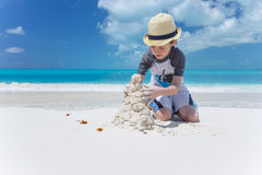 Little child making sand castle at the beach Stock Photos