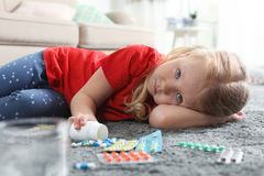Little child with many different pills on floor. Danger of medicament intoxication royalty free stock photo