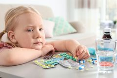 Little child with many different pills at table. Danger of medicament intoxication royalty free stock image