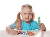 Little child with many different pills on white. Danger of medicament intoxication royalty free stock photography
