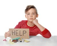 Little child with many different pills and word Help written on cardboard. Danger of medicament. Little child with many different pills and word Help written on stock photography