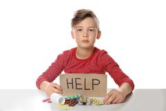 Little child with many different pills and word Help written on cardboard. Danger of medicament. Little child with many different pills and word Help written on royalty free stock photo