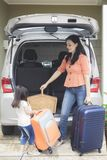 Little child and mother preparing for holiday. Portrait of little child helping her mother to carrying a suitcase into car while preparing for holiday, shot in Stock Photography