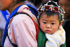 Little child on mother's back to the market Royalty Free Stock Images