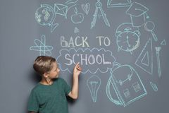 Little child near drawings and text BACK TO SCHOOL. On grey background royalty free stock images
