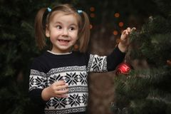 A little child by the New Year tree. Children decorate the Chris. Tmas tree. Baby in a sweater by a green tree in studio.r Stock Photos