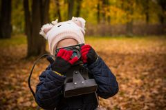 Little child with old retro camera doing photo outdoors.Portrait of little girl child with retro vintage reflex camera royalty free stock photo