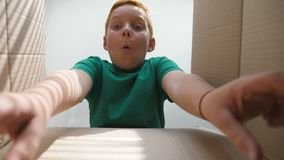 Little child opens carton box and pulling out gift from it. Small red-haired boy looking in parcel box and happy to. Receiving a surprise. Young kid showing joy stock video