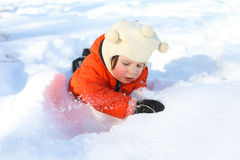 Little child in orange jacket plays with snow Stock Images