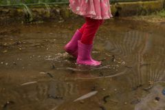 Playful little girl outdoor jump into puddle in pink boot after rain. Conceptual image. royalty free stock image