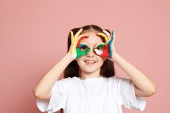 Little child with painted hands. On color background royalty free stock image