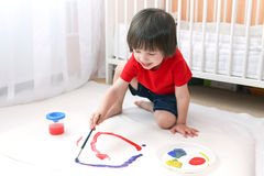 Little child painting with brush and gouache on floor at home Royalty Free Stock Photos