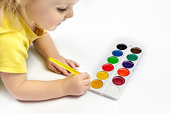 Little child painting with brush and watercolor on white background Stock Photo