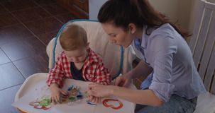 Little Child Painting with Hands and Developing Creativity and Fine Motor Skills. Indoors stock video footage