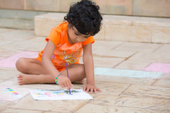Little Child Painting on a Patio. Outdoors Royalty Free Stock Photos