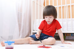 Little child paints with brush and gouache on floor at home Stock Images