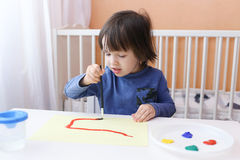 Little child paints with brush and gouache Royalty Free Stock Photos