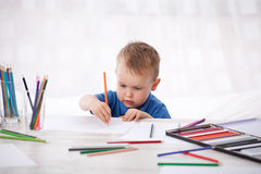 Little child paints with pencils. Little boy paints pictures with colored pencils royalty free stock image