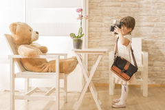 A little child photographer is taking a photo to her teddy bear Stock Photos