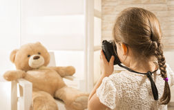A little child photographer is taking a photo to her teddy bear Royalty Free Stock Image