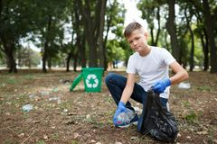 A little child picking up the garbage and putting it in a black garbage bag on a natural background. Ecology protection. A full-length portrait of a boy sitting royalty free stock images