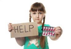 Little child with pills and word Help written on cardboard. Danger of medicament intoxication. Little child with pills and word Help written on cardboard against stock photography