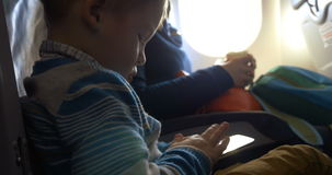 Little child in plane using smartphone. Little boy traveling by plane. He using smart phone to entertain himself during long and boring flight stock footage