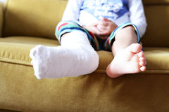 Little child with plaster bandage on leg heel fractured. Little girl with a white cast protecting her fractured leg Stock Images