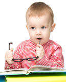 Little child play with book and glasses Stock Photos
